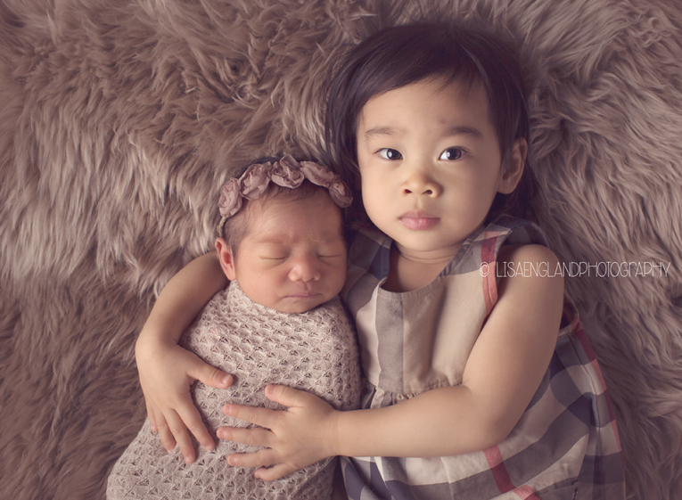 big sister holding her new baby sister
