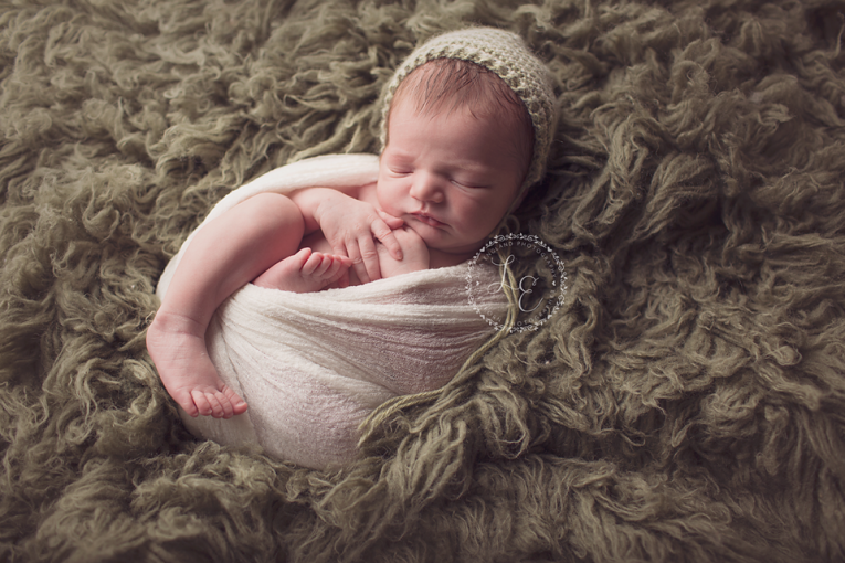infant boy on green rug